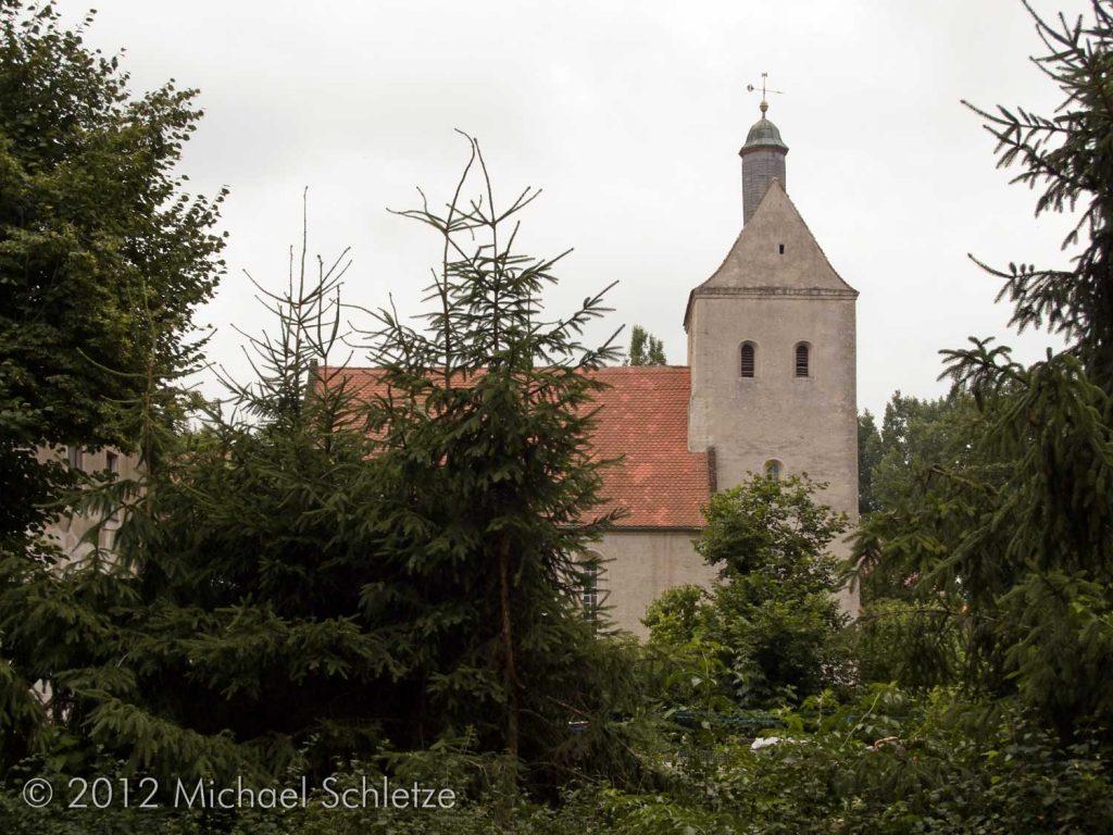 Verborgen hinter Bäumen, Sträuchern und Putz: Der hochmittelalterliche Backsteinkern der Altenauer Dorfkirche