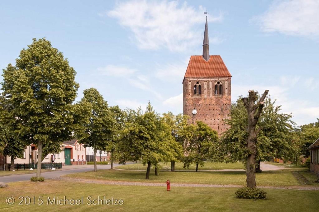 Turm der Uenzer Dorfkirche über dem breiten Anger