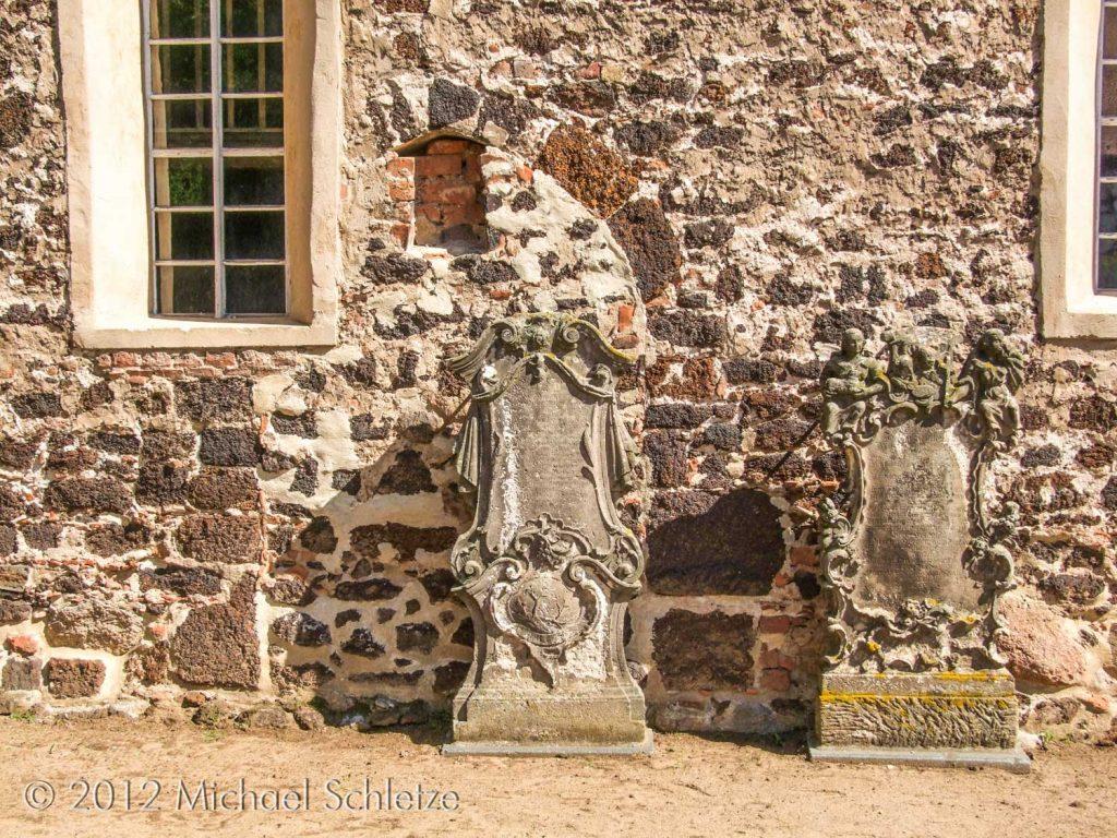 Vermauertes Spitzbogenportal auf der Südseite und barocke Grabsteine